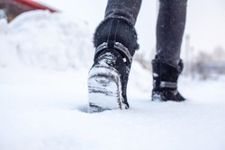 A person is walking on a slippery road, the first snow in the park, winter shoes, the road is covered with slippery ice and white snow. Footprints and shoes close-up.