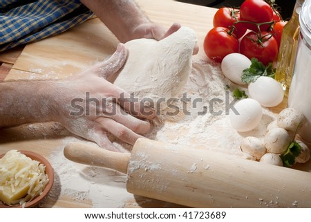 A person kneading dough on table top with fresh tomatoes, flour and cheese