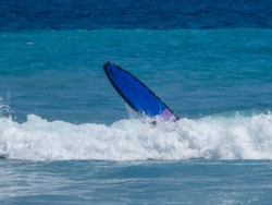 A person learning how to surf on an open sea. The surfing board is rocketing high up above the waves. Difficult conditions for beginner surfers.