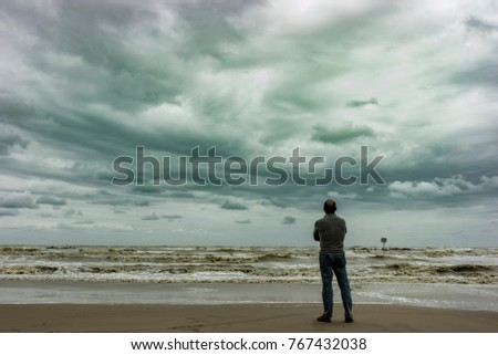 A person looking at the horizon during a stormy day on the beach