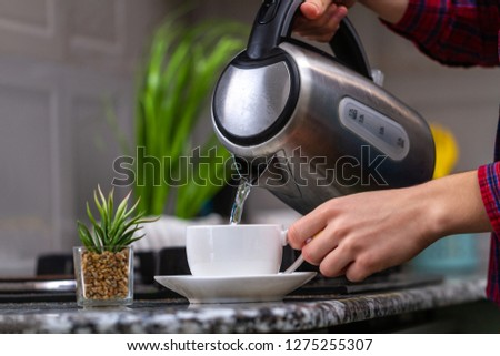 A person makes tea using boiling water from an electric kettle in kitchen at home. Time for breakfast