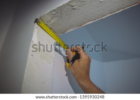A person measuring width and height of a door opening with a yellow tape measure. New house construction measurements