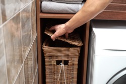 A person opens a lid of a Wicker laundry basket near a Modern washing machine in a laundry room. Scandinavian Interior of laundry room.