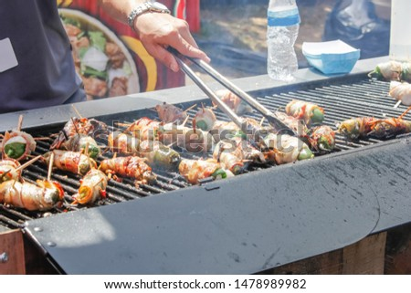 A person prepares bacon wrapped jalapeño poppers on the grill #1478989982