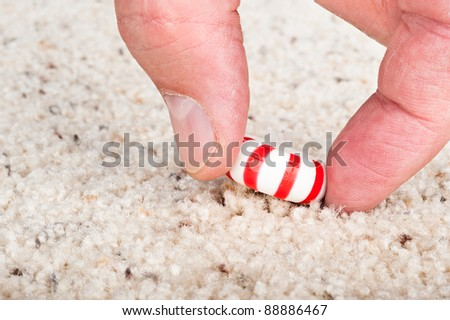 A person pulling a sticky candy mint off the carpet.