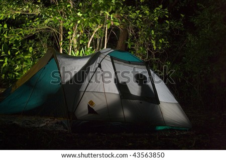 A person reading in a tent. - stock photo