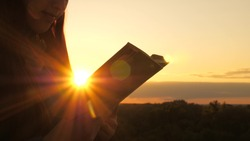 A person reads a book in the sun. Man reads Bible outdoors. A man holds Bible in his hands and studies the word of God at sunrise on top of mountain. Searching for truth in scriptures.