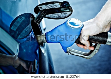 a person refueling a car at a gas station - stock photo