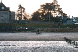 A Person Riding A Bike On The Malahide Beach