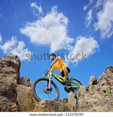 A person riding a mountain bike on a sunny day, low angle view