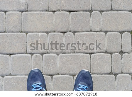 A person's feet in sports shoes on pavement. Cropped image. #637072918