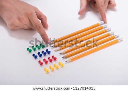 A Person's Hand Arranging Pencils And Multi Colored Pushpins In A Row On White Background