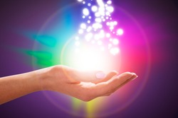 A Person's Hand Into Magical Healing Energy Field With Multi Colored Glowing Lights