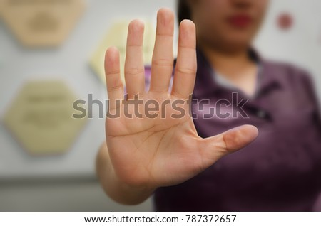 A person showing an open hand signal that means stop or wait isolated on a blurred background