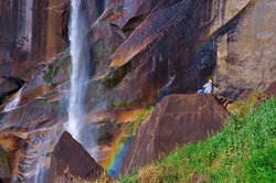 A person sits at the base of a waterfall looking in awe at the magnificent beauty of Creation