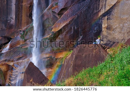 A person sits at the base of a waterfall looking in awe at the magnificent beauty of Creation Stock photo ©