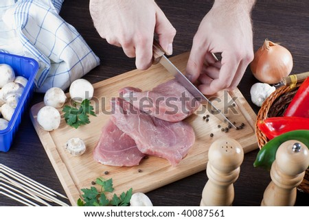 A person slicing raw pork meat on wooden board