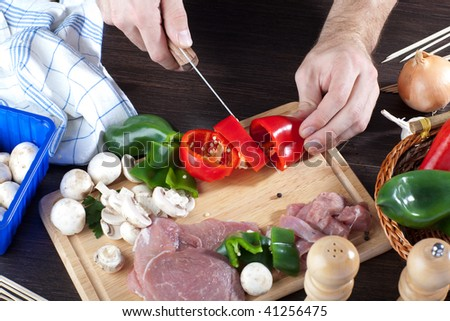 A person slicing red bell peppers on wooden board with some meat and mushrooms around it