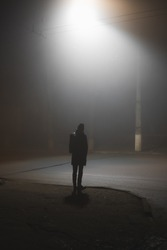 A person standing near the road in a foggy town at night. Noir aesthetics, concept of loneliness, dullness and late autumn mood