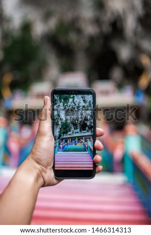 a person take a picture of Batu Caves at stairs.  in the background of Batu Caves, near Kuala Lumpur, Malaysia. Traveling with children concept.