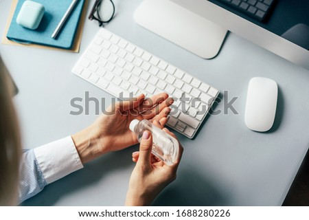 A person treats hands with a disinfector over a working office desk. Self-isolation and hygiene in the epidemic of coronavirus. Stay at home in quarantine and work remotely from home.