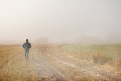A person walk into the misty foggy countryside, rural road in a dramatic mystic sunrise scene with abstract colors