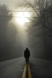 A person walk into the misty foggy forest road in a dramatic  sunrise scene