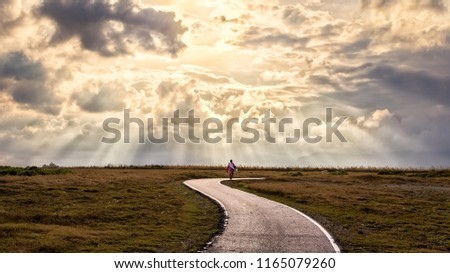 A person walking alone along s-shape path. The sun produces amazing light rays across the sky. The image is simple and breathtaking. This image is suitable for background use or add quote above. #1165079260