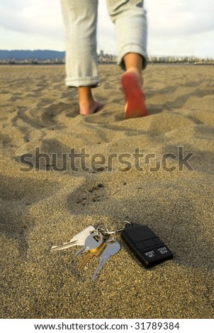 A person walks away, leaving their keys in the sand at the beach.