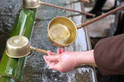 A person washing hands with saint water in a Japanese temple, Tokyo