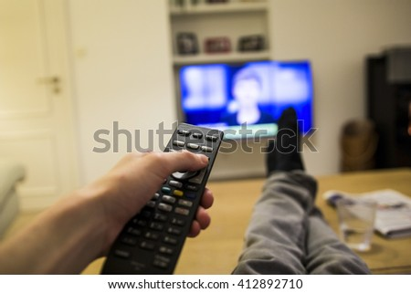 A person watching the news on TV with the feet on the table and a remote in the hand.