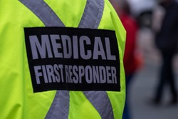 A person wearing a medical first responder's jacket made of bright yellow waterproof material with a grey reflective cross with the words medical first responder There are people in the background.