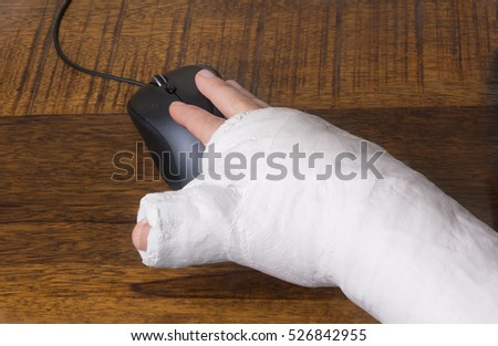 A person wearing an arm cast after breaking their wrist having difficulty using a computer mouse - Shutterstock ID 526842955