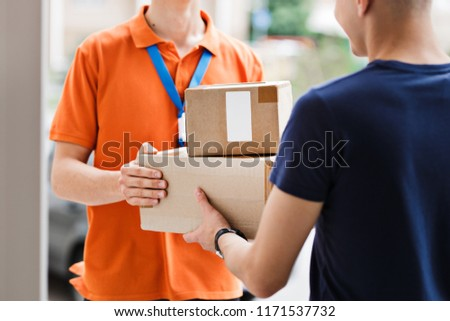 A person wearing an orange T-shirt and a name tag is delivering