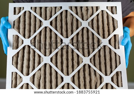 A person wearing blue gloves is holding a heavily clogged dirty air filter in hands before replacing it with the new one. Paper based, card board frame plated filters are used in hvac, ac , furnaces. Foto stock ©