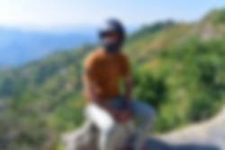 A person wearing helmet sitting outside the road with blur effect