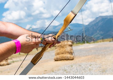 A person with a bow and an arrow aiming to shoot a bullseye. #1443044603