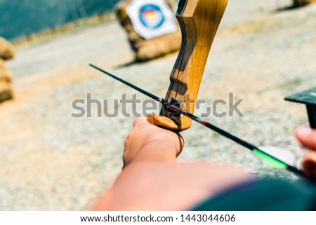 A person with a bow and an arrow aiming to shoot a bullseye. #1443044606