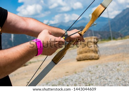 A person with a bow and an arrow aiming to shoot a bullseye. #1443044609