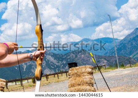 A person with a bow and an arrow aiming to shoot a bullseye. #1443044615