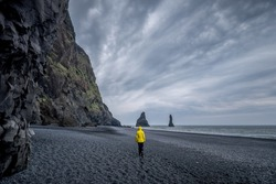 A person with a yellow jacket walking on the beach surrounded by rocky cliffs under storm clouds in Iceland
