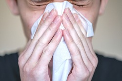 A person with symptoms of the disease presses a handkerchief to his face. Sneezing, bouts of coughing.