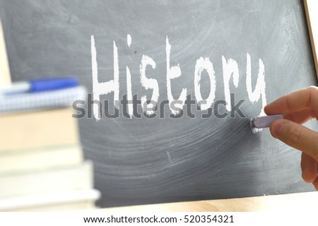 A person writing in a blackboard during History class in a school.  #520354321