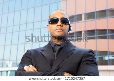 A personal security guard, arms folded