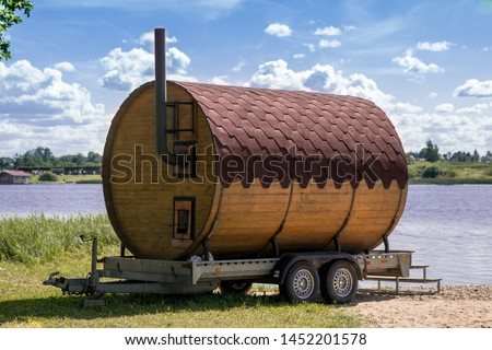 A personal small hotel sauna in the woods on the Baltic river shore with  blue sky and big river. Round-wooden sauna, mobile compact bath in the form of a wooden barrel. Finnish SPA, relax holidays