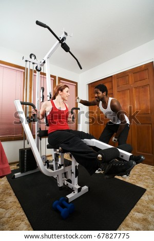 A personal trainer encourages his student to work out harder. Working out on weight training equipment