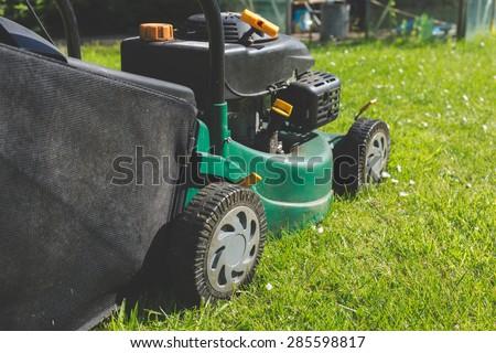 A petrol lawn mower cutting an overgrown lawn. #285598817