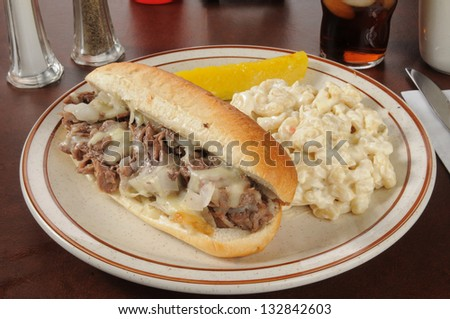 A Philly cheese steak sandwich with macaroni salad