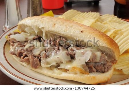A philly cheese steak sandwich with potato chips