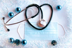 a phonendoscope and a medical mask on a light background with New Year's tinsel and toys. Health care and medicine concept.